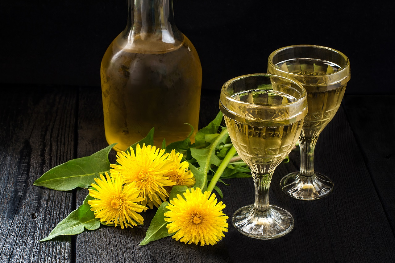 Cooled-homemade-dandelion-wine-in-old-wineglasses-bottle-and-wreath-from-dandelions-on-a-dark-background