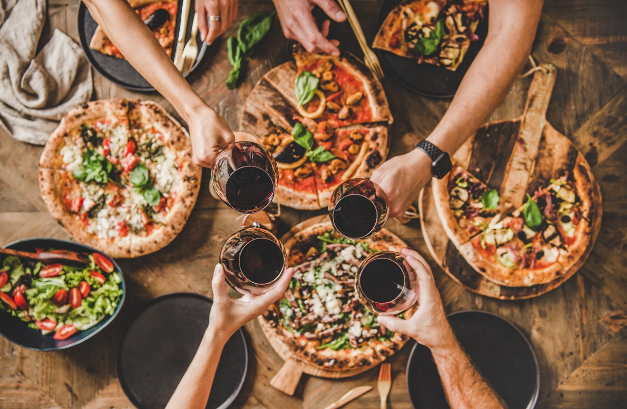 Family-or-friends-having-pizza-party-dinner.-Flat-lay-of-people-clinking-glasses-with-red-wine-over-rustic-wooden-table-with-various-kinds-of-Italian-pizza