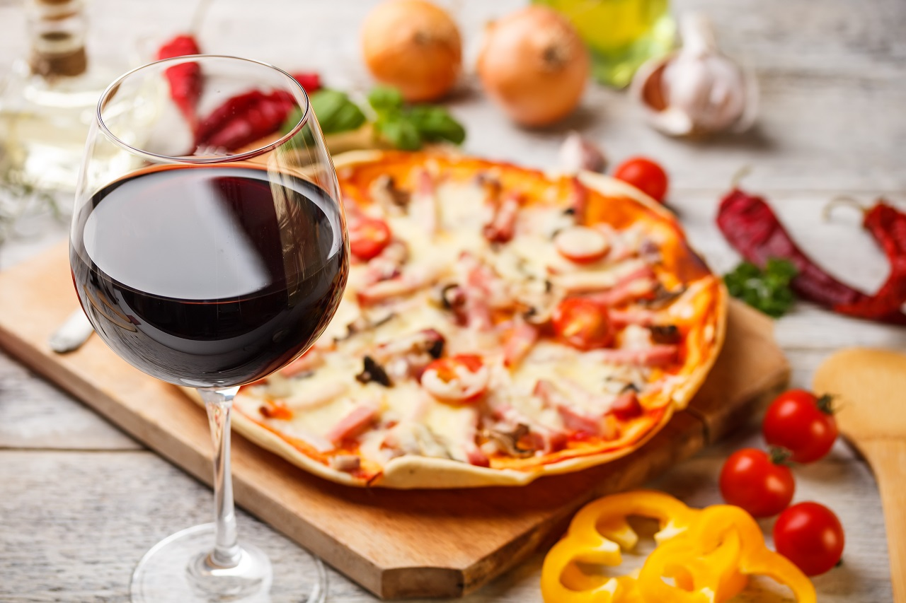 Glass-of-red-wine-with-pizza-on-cutting-board
