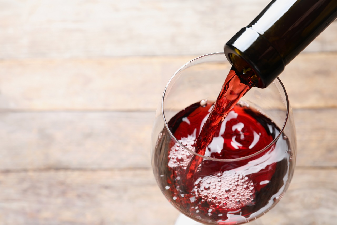 Pouring-red-wine-from-bottle-into-glass-on-blurred-background-closeup.-Space-for-text