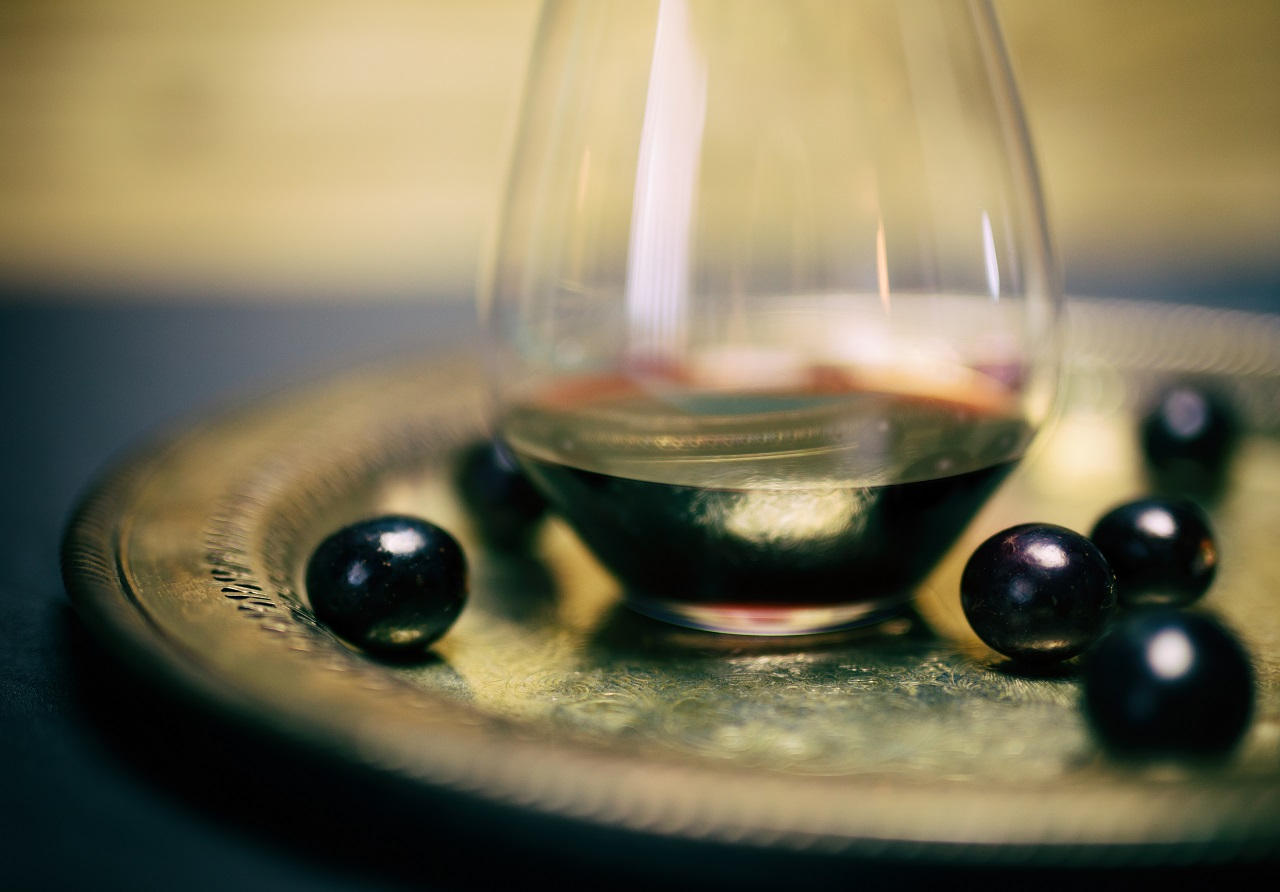 Red-wine-in-crystal-stemless-glass-with-Muscadine-grapes-on-silver-platter