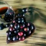 Red-wine-in-crystal-stemless-glass-with-wooden-heart-shaped-bowl-filled-with-Muscadine-grapes-on-burned-wooden-background
