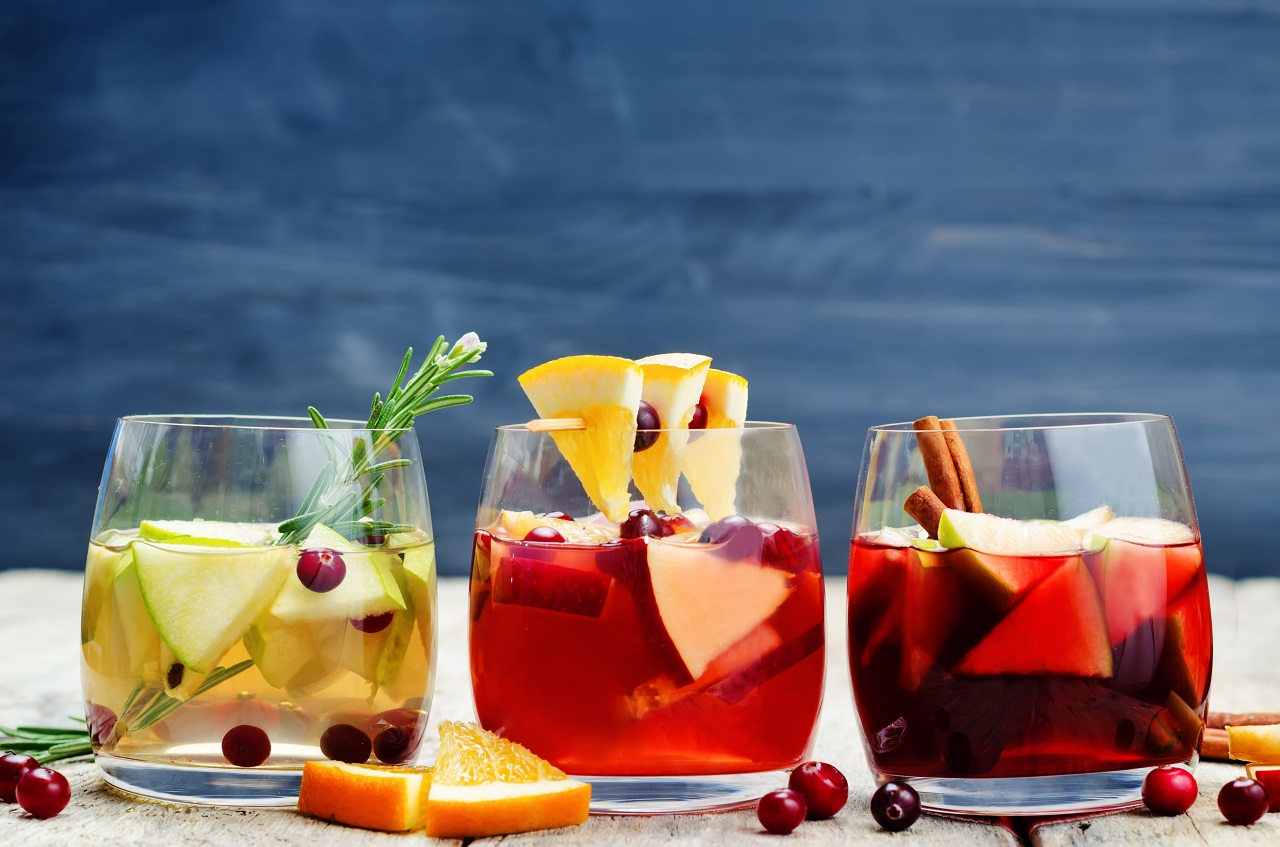 Traditional-summer-drink-sangria-red-pink-and-white.-With-champagne-pink-and-red-wine-strawberries-oranges-lemon-green-apple-and-grapefruit.-On-a-wooden-rustic-table-copy-space