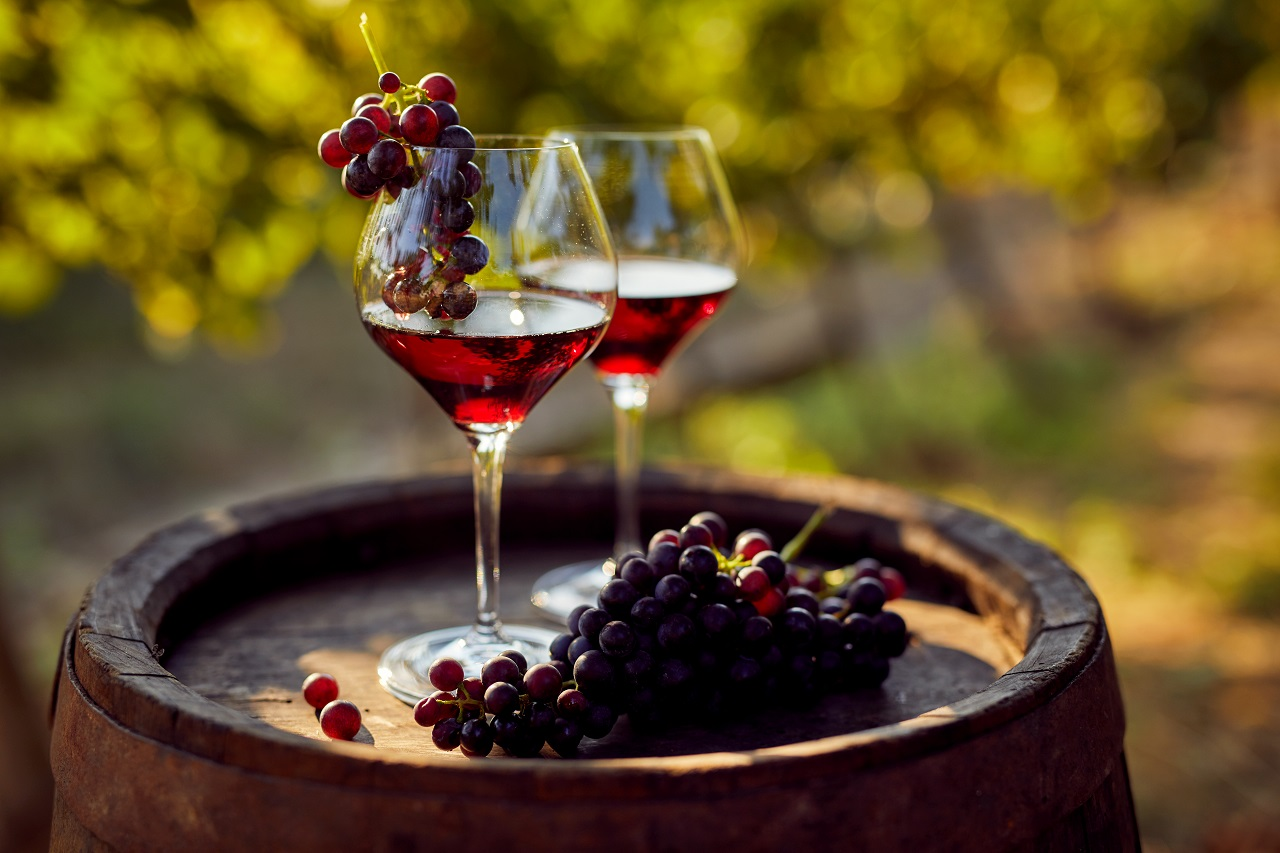 Two-glasses-of-red-wine-with-a-bottle-on-a-wooden-barrel