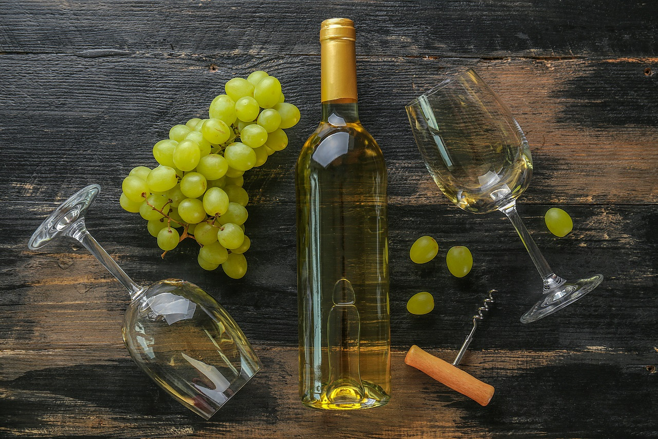 Unopened-vintage-bottle-of-white-wine-without-label-and-bunches-of-ripe-organic-grapes-on-grunged-wood-table-background.-Expensive-bottle-of-chardonnay-concept