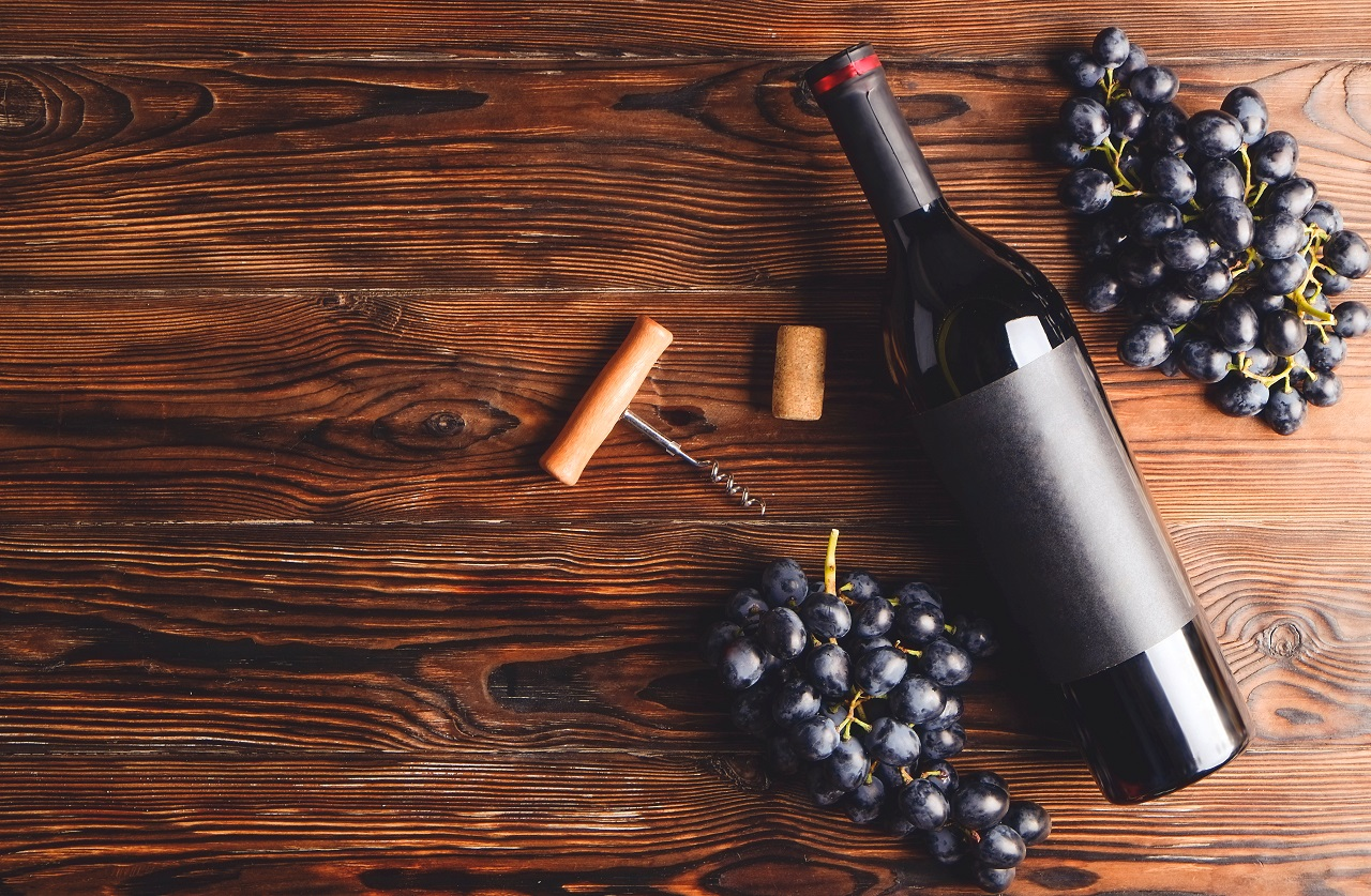 Vintage-bottle-of-red-wine-with-blank-matte-black-label-corkscrew-bunches-grapes-on-wooden-table-background.-Expensive-bottle-of-cabernet-sauvignon-concept