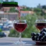 Waiter-pouring-red-wine-on-outdoor-cafe-terrace-in-sunny-summer-day-in-France