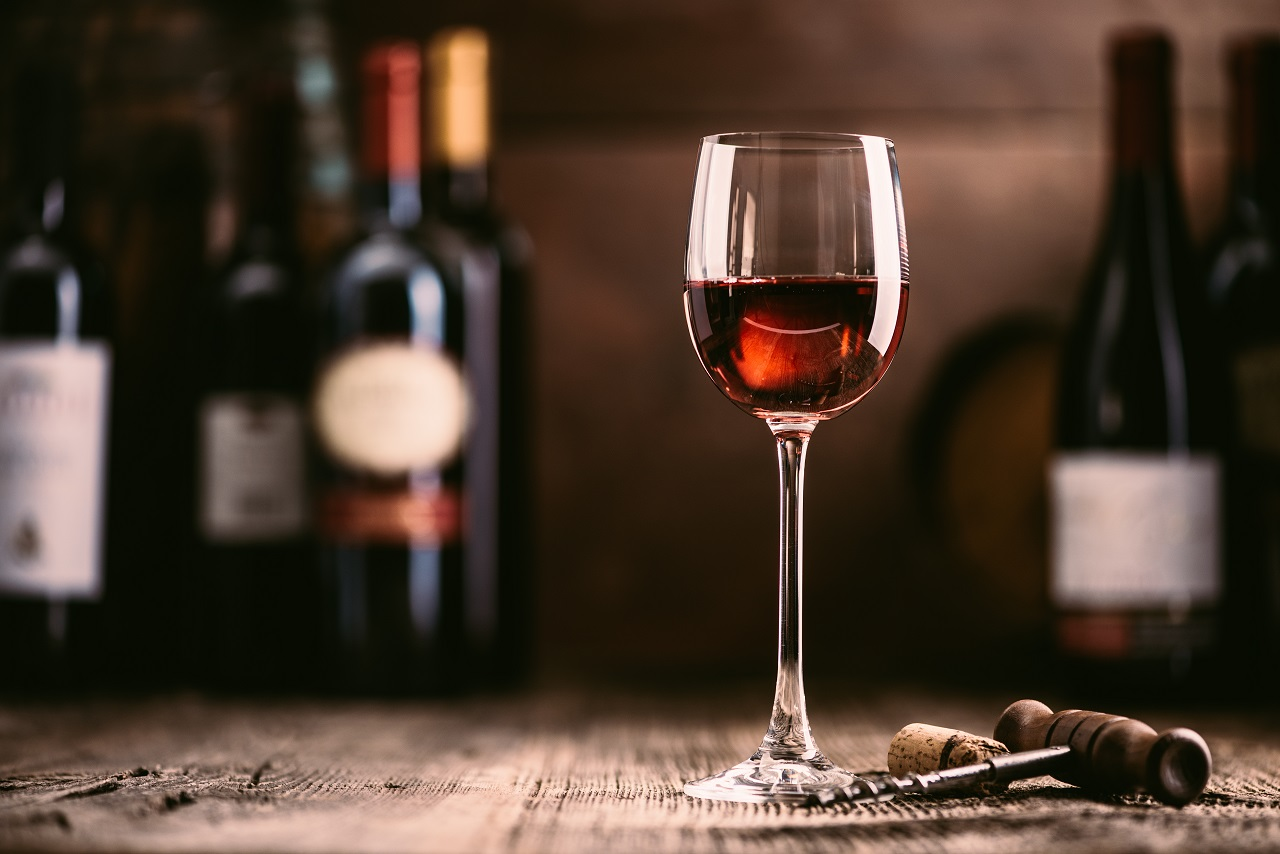 Wine-tasting-experience-in-the-rustic-cellar-and-wine-bar-red-wine-glass-and-collection-of-excellent-wines-on-the-background