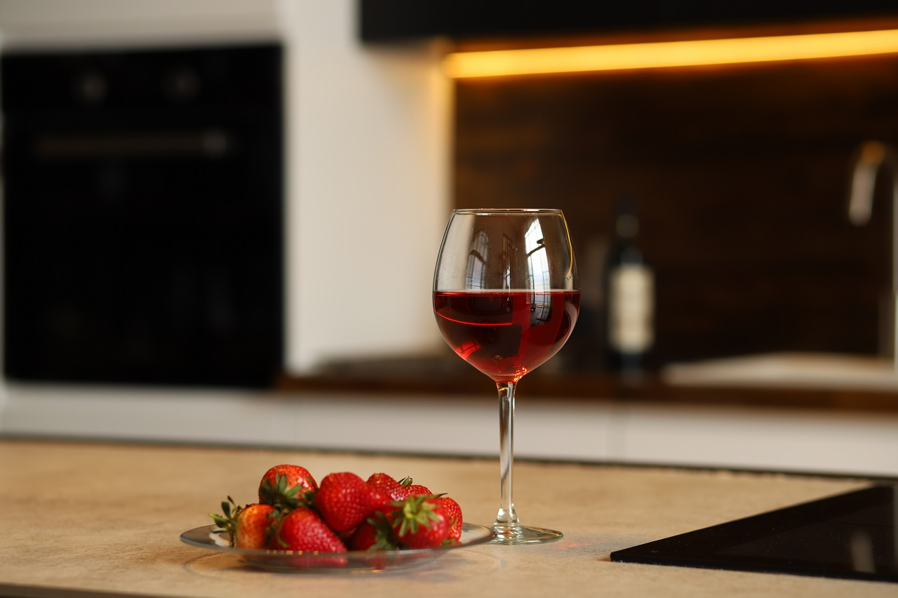 a-glass-of-wine-and-strawberries-on-the-kitchen-table